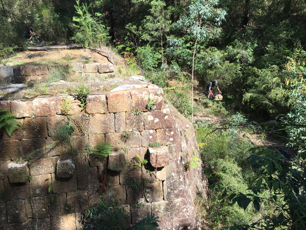 downward view of a stone block wall in the trees with a cyclist on a trail below