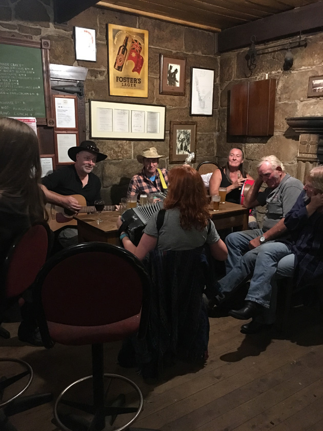 Two people with cowboy hats play guitars while sitting at table with a group people
