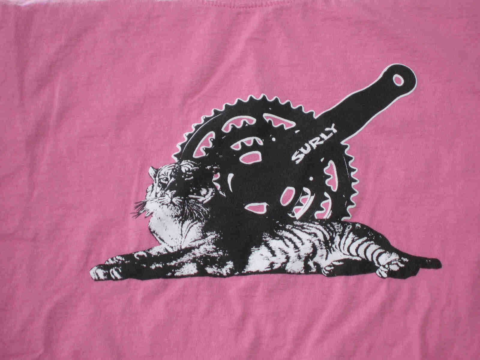 Front, chest area view of a pink Surly Bikes t-shirt with a graphic of a bike crank and a tiger