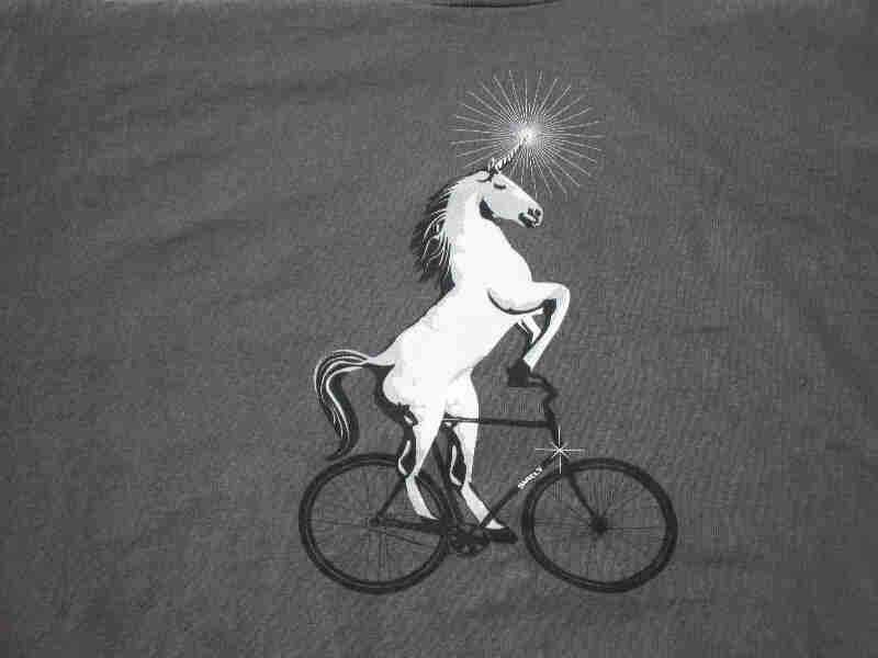 Front, chest area view of a gray Surly Bikes t-shirt with a graphic of unicorn riding a bike