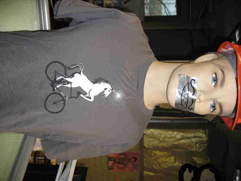 Waist up view of mannequin, wearing a gray Surly Bikes t-shirt with graphic of a unicorn riding a bike