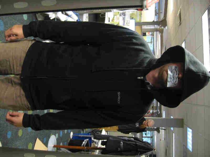 Front view of a person, wearing a black Surly Bikes Full Zip Hoodie, standing in an office with duct tape on their mouth