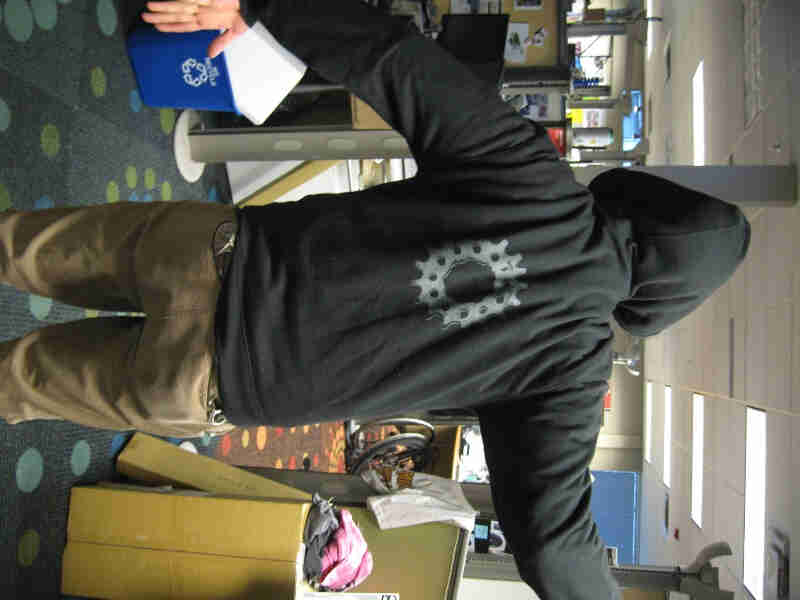 Rear view of a person, wearing a black Surly Bikes Full Zip Hoodie with a bike gear graphic, standing in an office