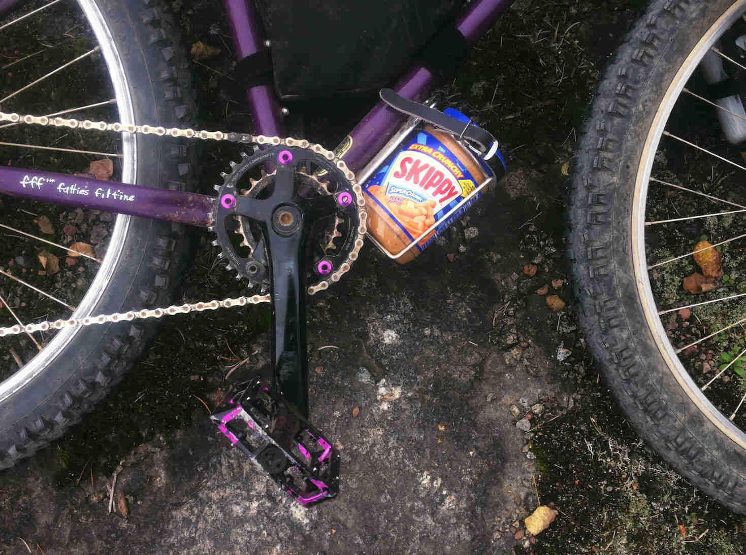 Downward view of the cranks and waterbottle cage with Skippy peanut butter jar, on a purple Surly bike on it's left side