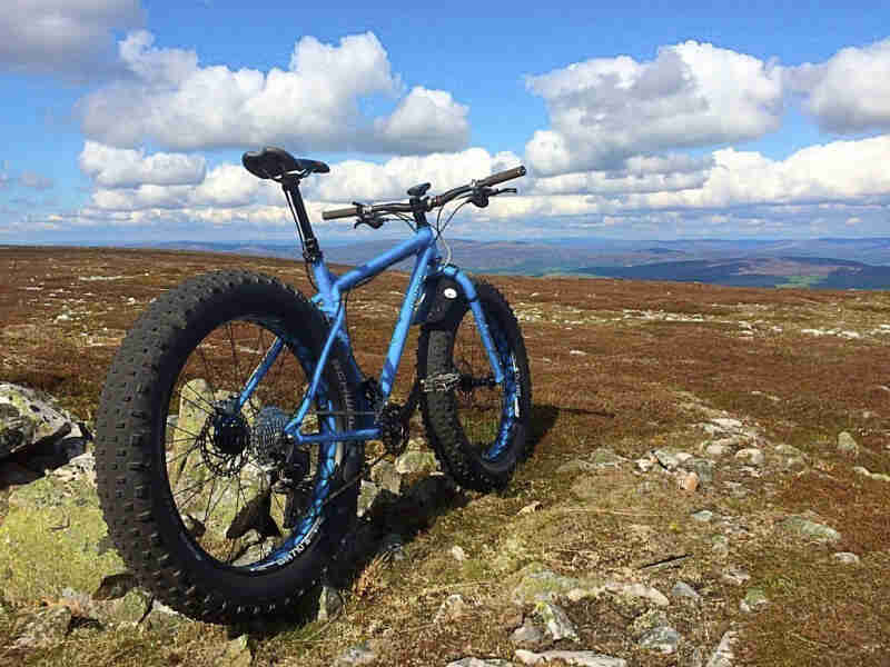 Rear view of a blue Surly fat parked on rocky field, with blue sky and white cloud above