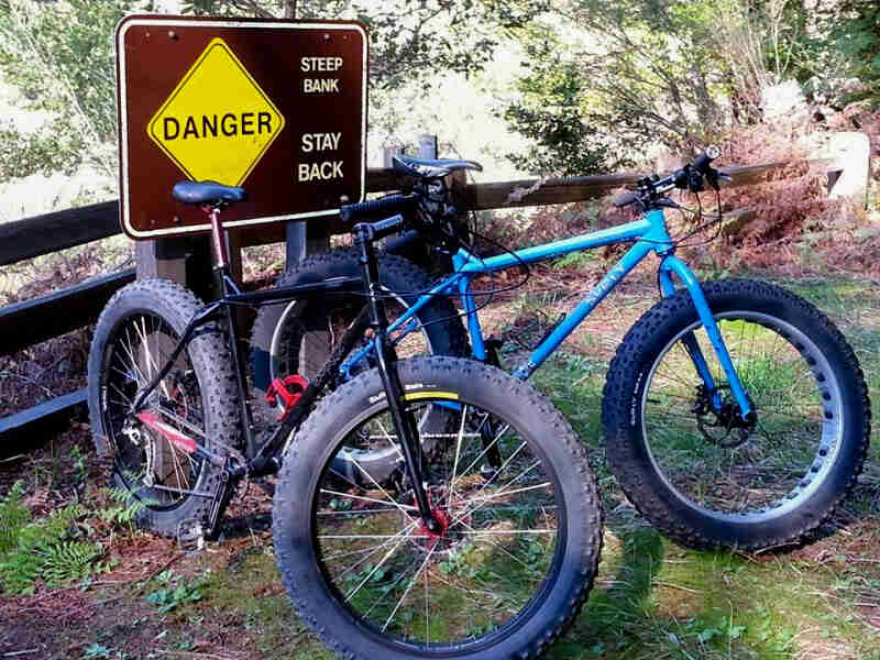 Front right view of 2 Surly Ice Cream Truck fat bikes, side by side, parked in front of Danger sign and a wood fence