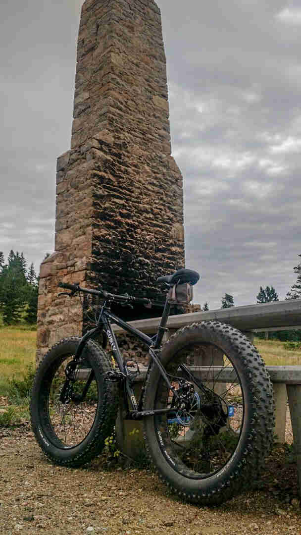 Rear left side view of a Surly Ice Cream Truck fat bike, black, parked on gravel in front of an outdoor stove with stack