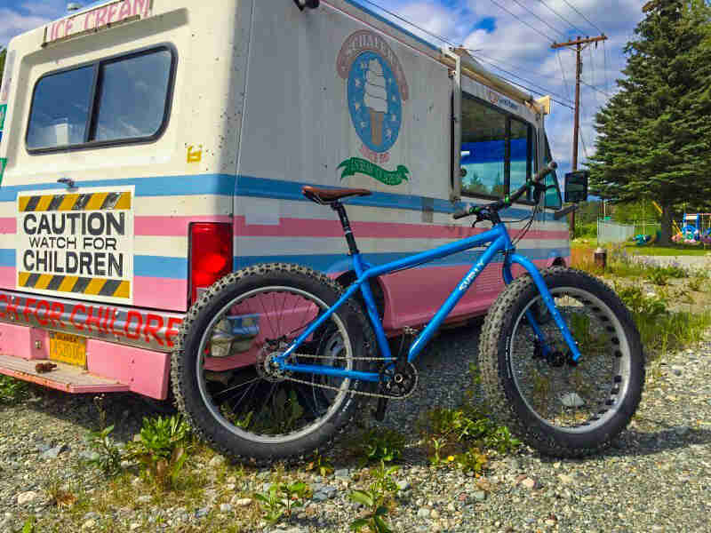 Right side view of a Surly Ice Cream Truck fat bike, blue, parked on gravel next to an Ice Cream Truck vehicle