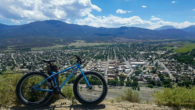 Right side view of a Surly Ice Cream Truck fat bike, blue, parked on hilltop, and a city with below with mountain behind