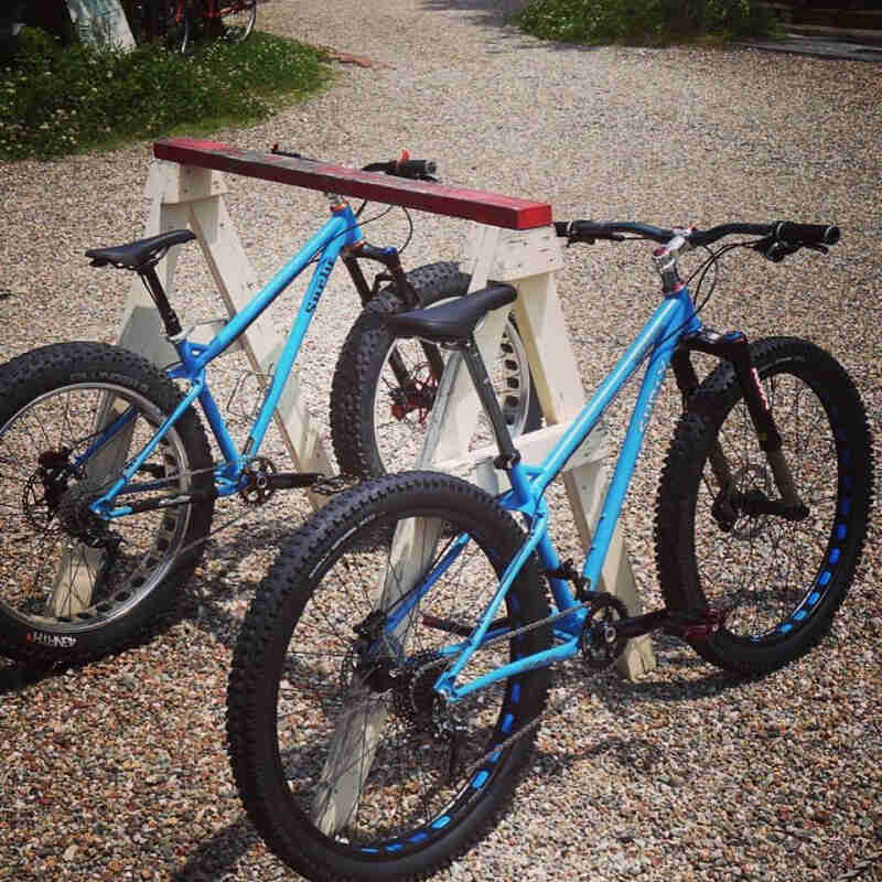 Right rear angle view of 2 Surly Ice Cream Truck fat bikes, parking on gravel, leaning against a sawhorse