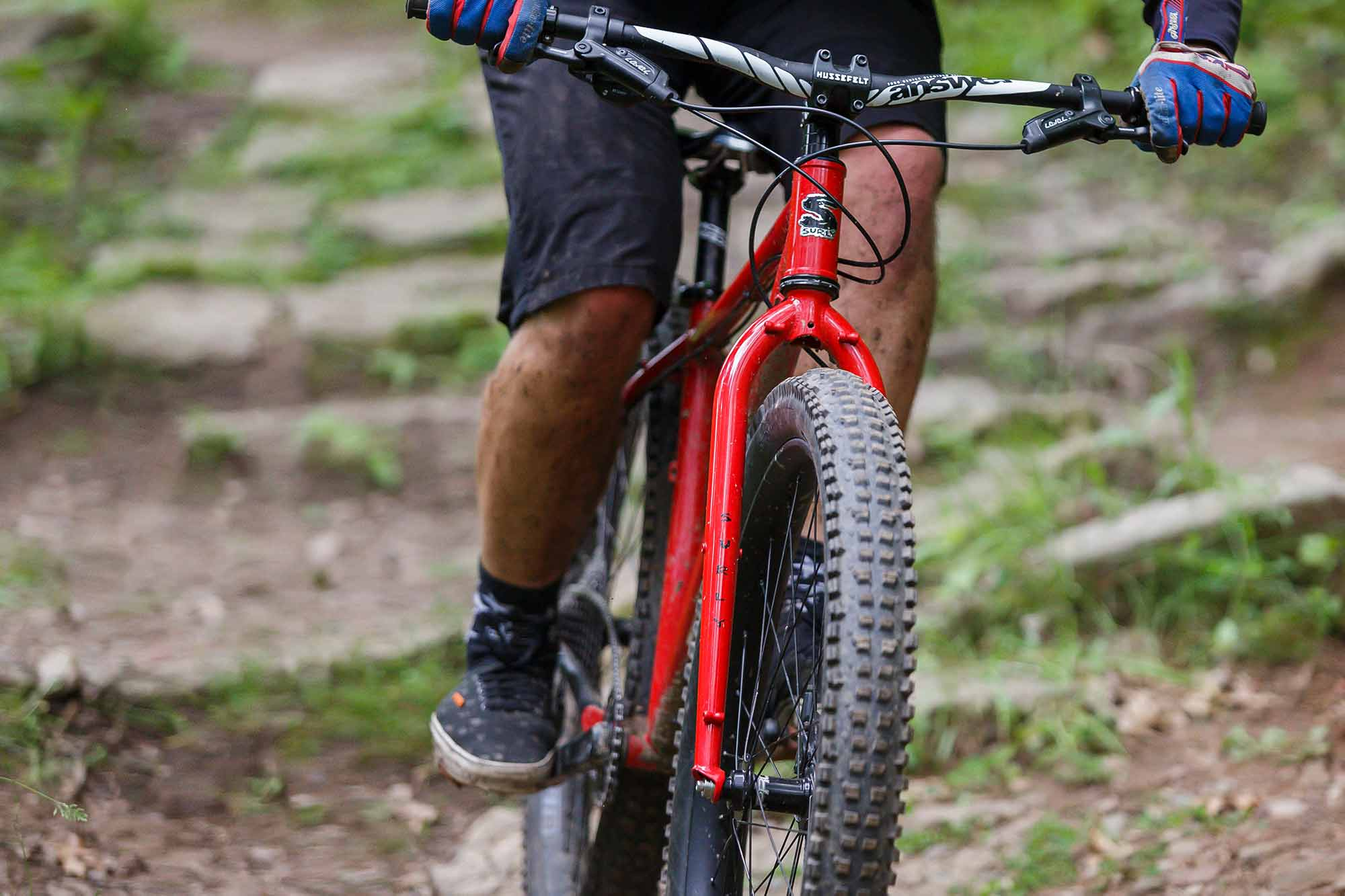 Mountain biker on rocky off-road trail riding red Surly Krampus showing large Surly Dirt Wizard tires on wide rims