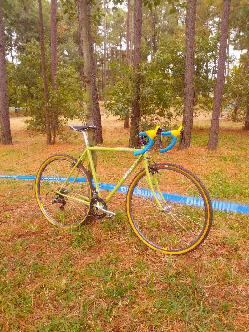 Right side view of a lime green Surly bike, leaning on a tree with race course tape wrapped around it, in a pine forest