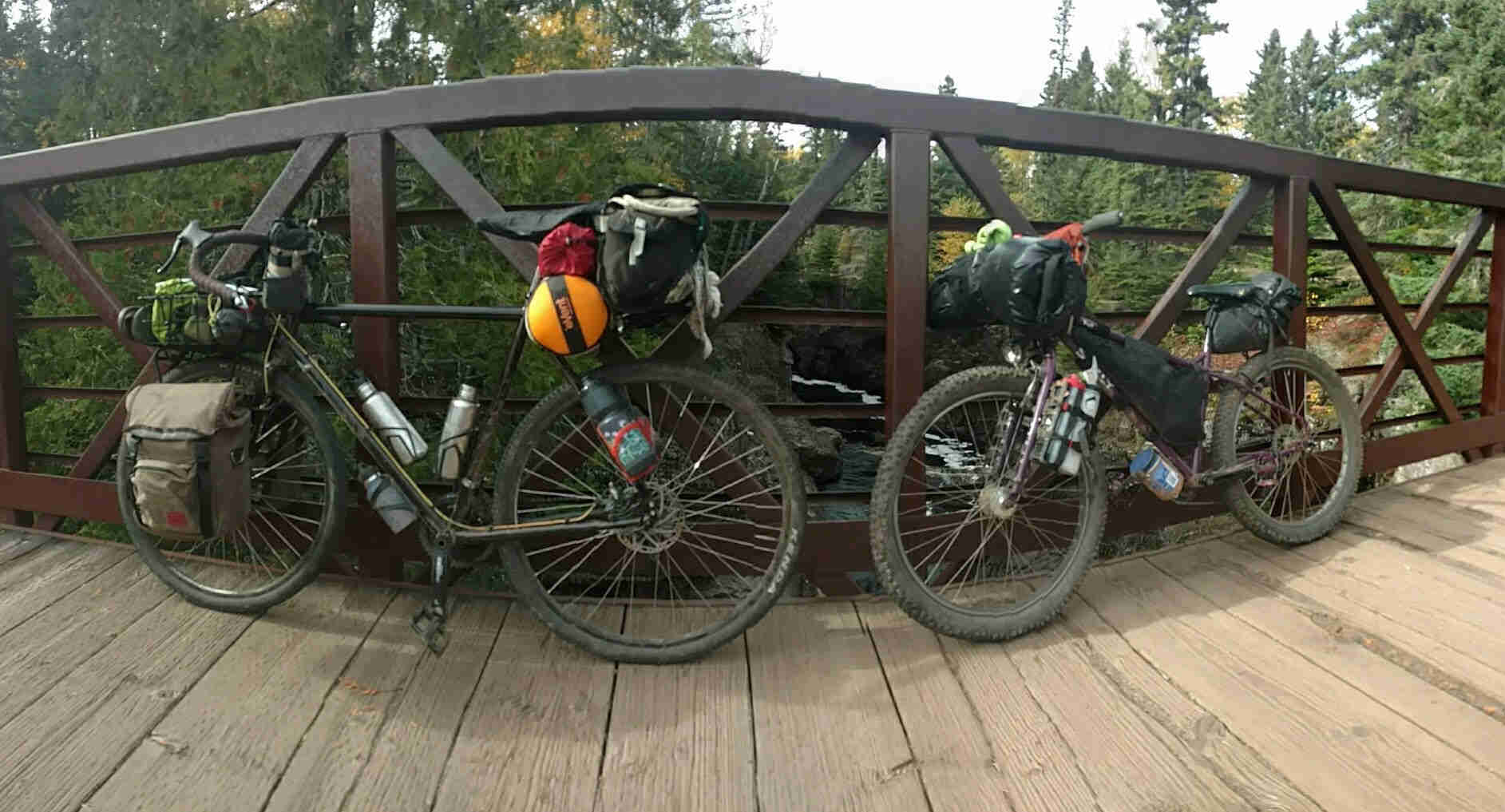 Left side view of 2 Surly bikes, loaded with gear, leaning on steel rail of a wood bridge over a river with trees surrounding it