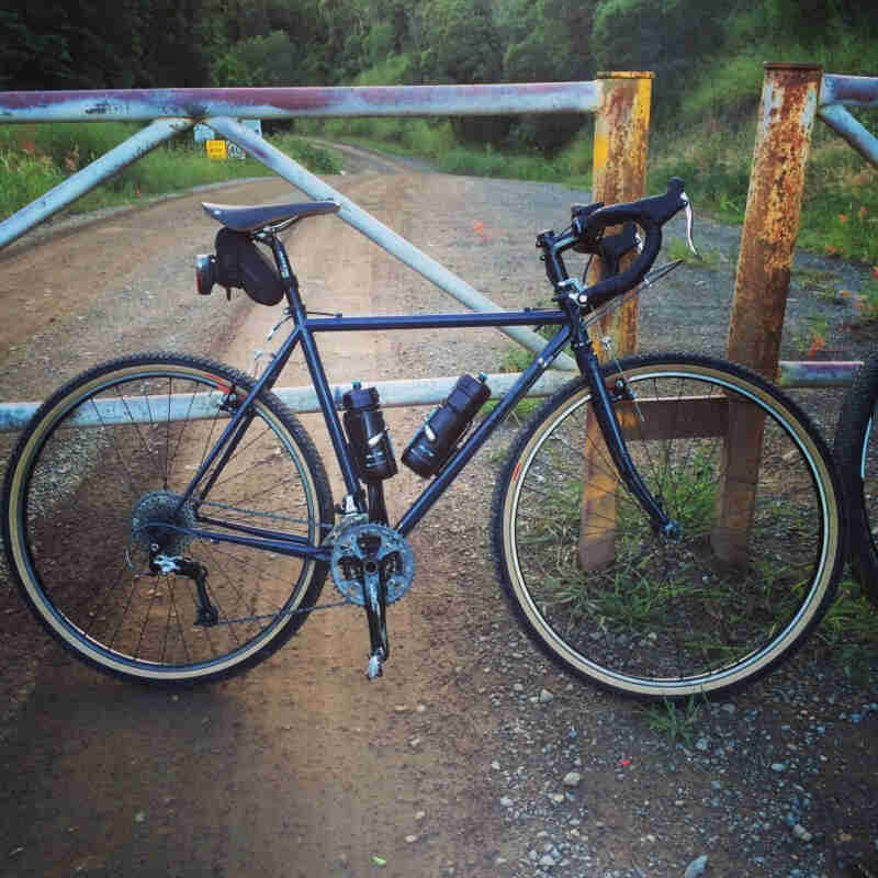 Right side view of a blue Surly Cross Check bike, parked on a gravel road in front of a closed gate