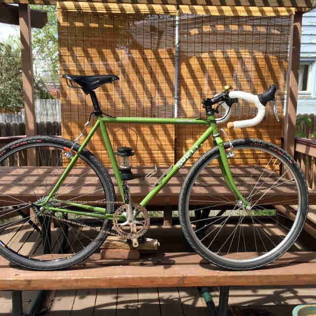 Right side view of a green Surly Cross Check bike, parked on a picnic table under a pergola
