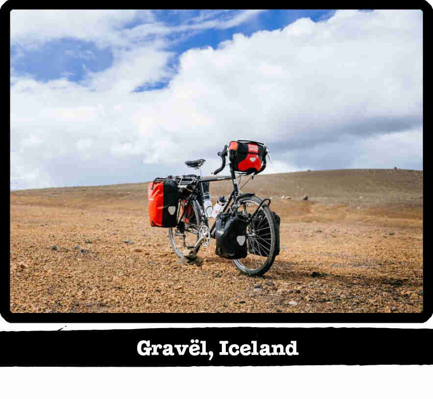 Front left view of a Surly Long Haul Trucker bike loaded with gear, in a pebble field-Gravel, Iceland banner below image