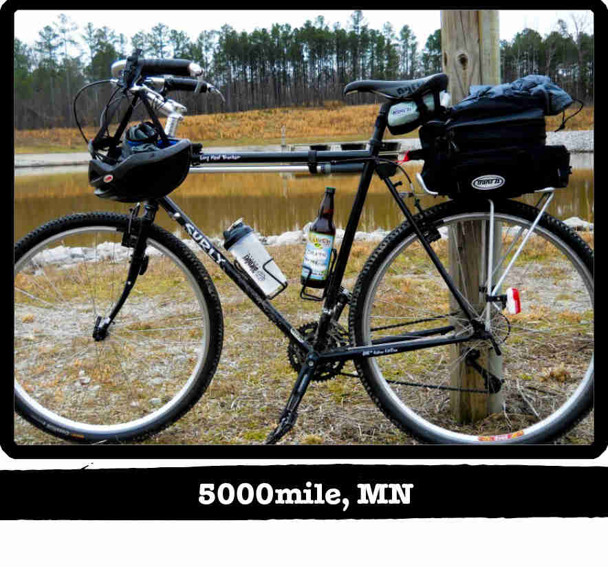 Left side view of a black Surly Long Haul Trucker bike with gear, in front of a pond - 5000mile, MN tag below image