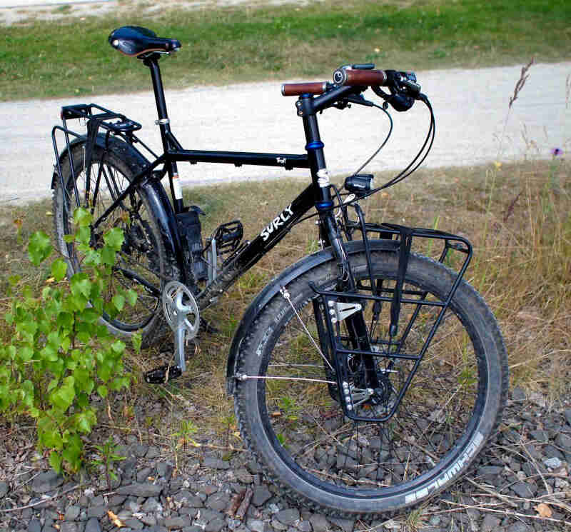 Front view of a black Surly Troll bike with it's front wheel turned to the left, standing on grass and rocks