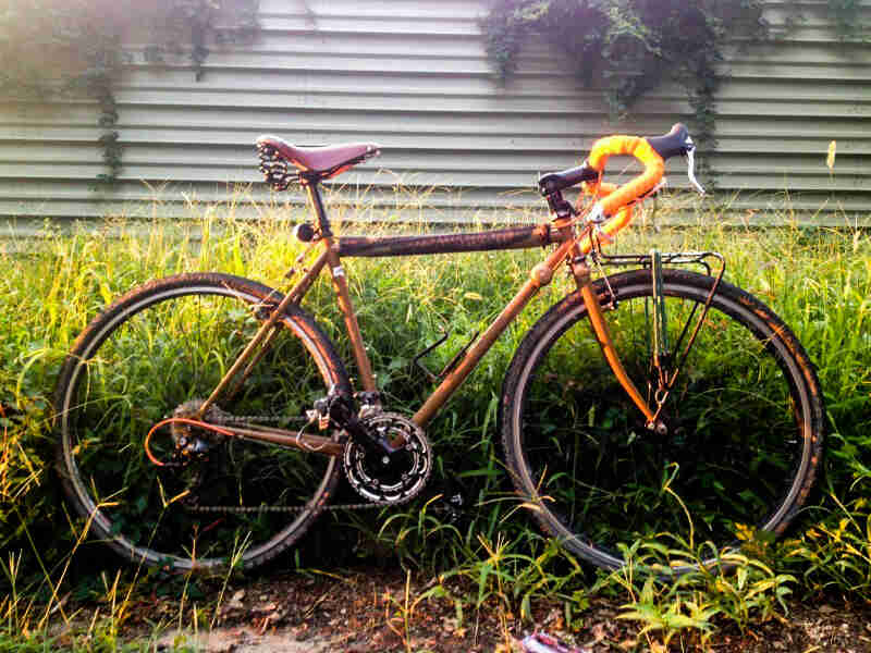 Right side view of an orange/purple Surly Cross Check bike, parked along tall weeds, with a steel wall in the background