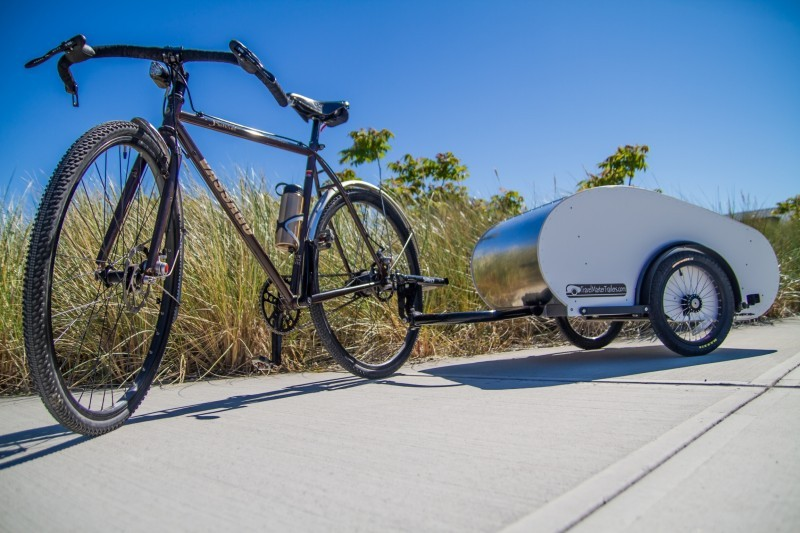 Left side view of a black bike with a hardcover trailer, parked on a cement slab with weeds behind it