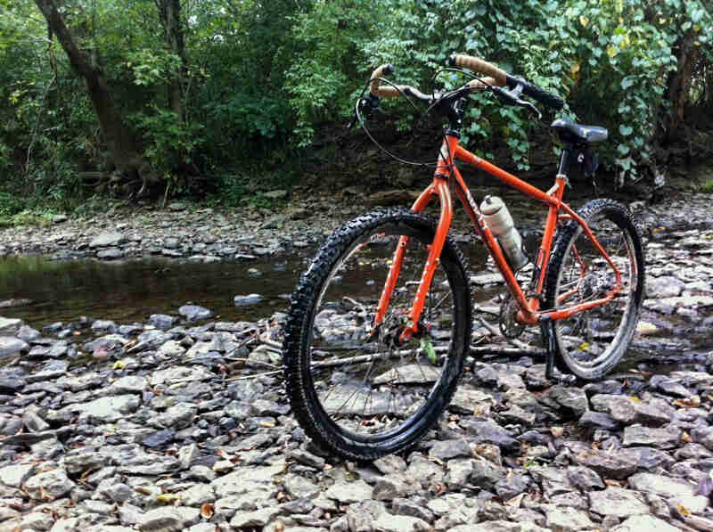 Front left side view of an orange Surly Troll bike, on the rocks of a stream bed, with the green woods in the background