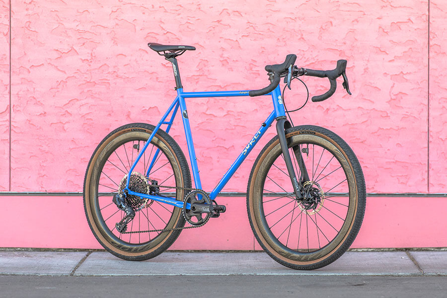 Right side view of a Surly Midnight Special Bike - Perry Winkle's Sparkle - on a sidewalk alongside a pink stucco wall