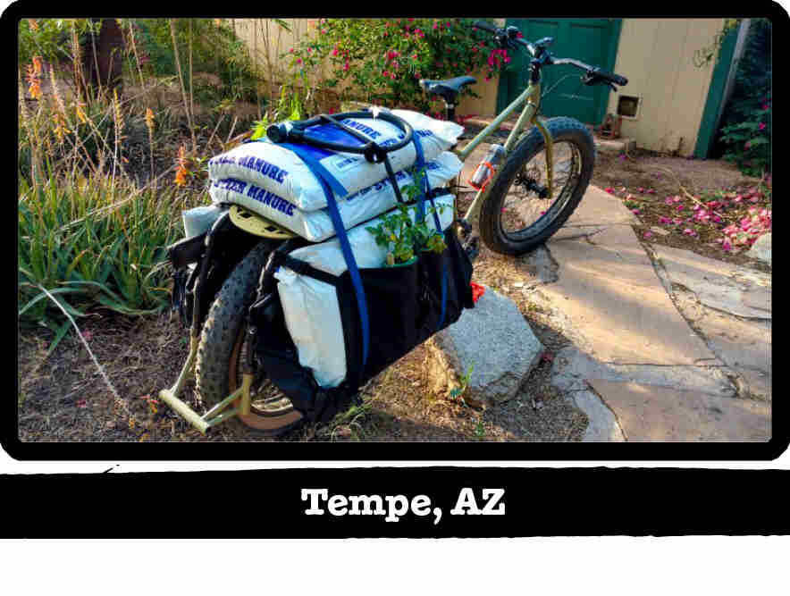 Rear view of a Surly Big Fat Dummy bike with bags of manure load on back, in front of a home - Tempe, AZ tag below image