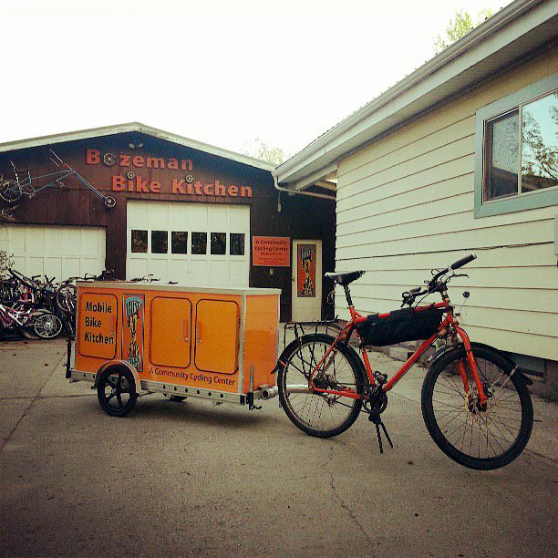 Right angled view of a Surly Troll bike with food trailer attached, in a driveway, with a garage in the background