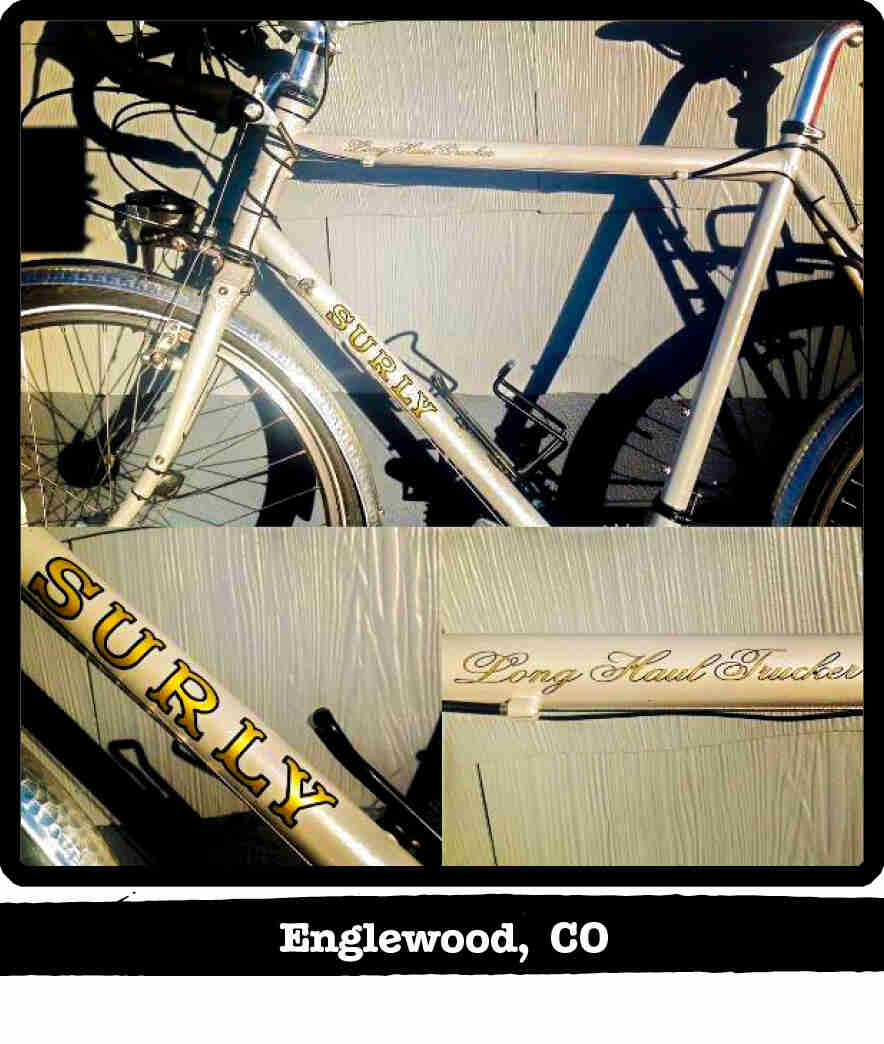 Left profile of a Surly Long Haul Trucker bike, tan, leaning of a wood-sided wall - Englewood, CO tag below image