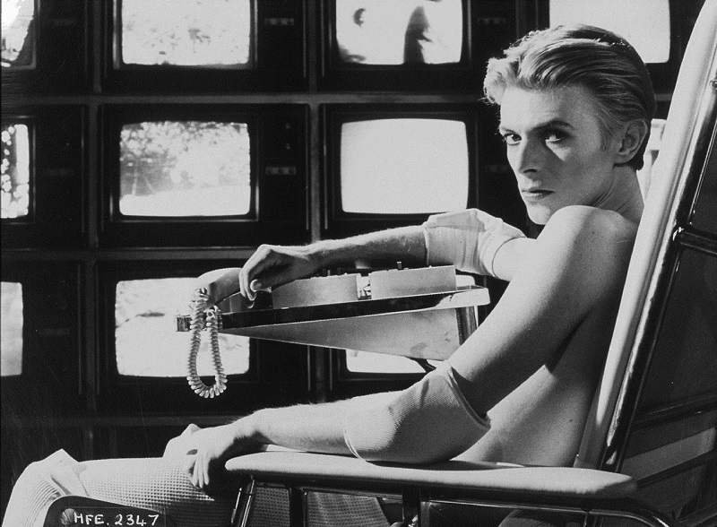Black and White photograph of David Bowie sitting in a chair with a wall of TVs in the background