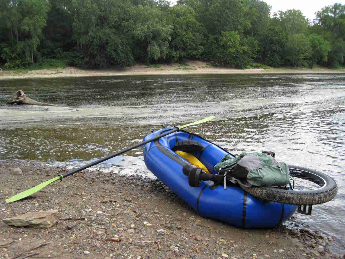 Rear view of a blue inflatable raft with an oar leaning on it, and a fat wheeled unicycle in the back, on a river bank