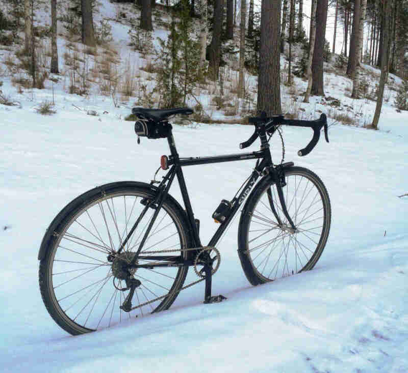 Right side view of a black Surly Cross Check bike, parked in a snowy trail, with a snowy forest hill in the background