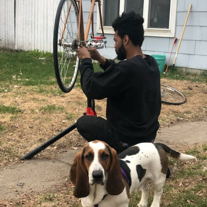 Cyclist squats down while fixing a drive chain on a bike with a basset hound