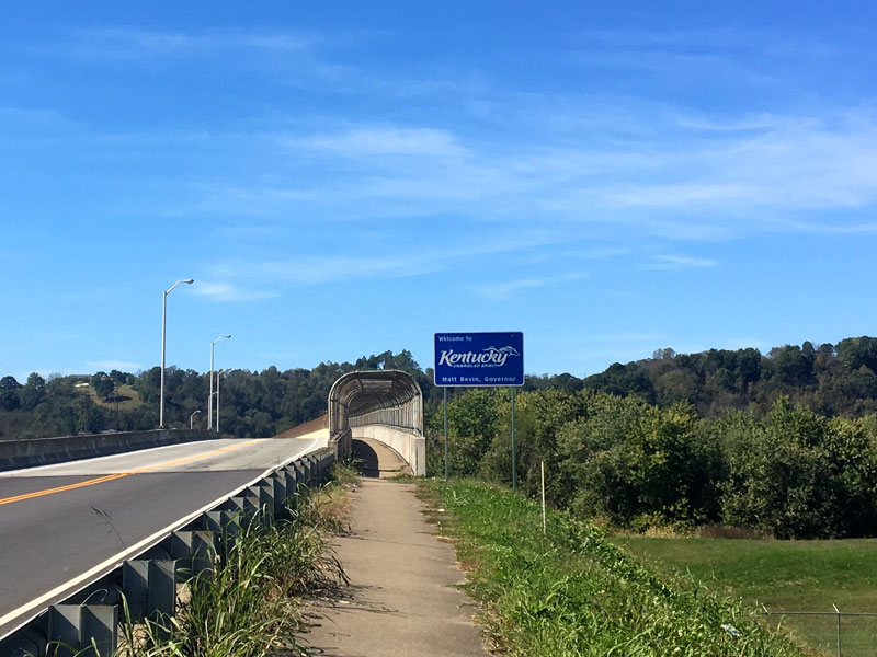 2 lane highway leading to a bridge with a bike trail and a Kentucky welcome sign on the right side with blue sky above